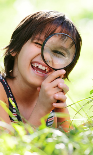 This photograph shows a very young book looking through a magnifying glass. The photograph is used as part of the Find a Speech Pathologist search