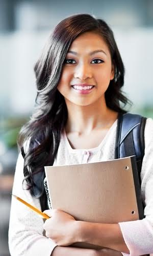 This is a photograph of a young lady who is a student holding her academic books.